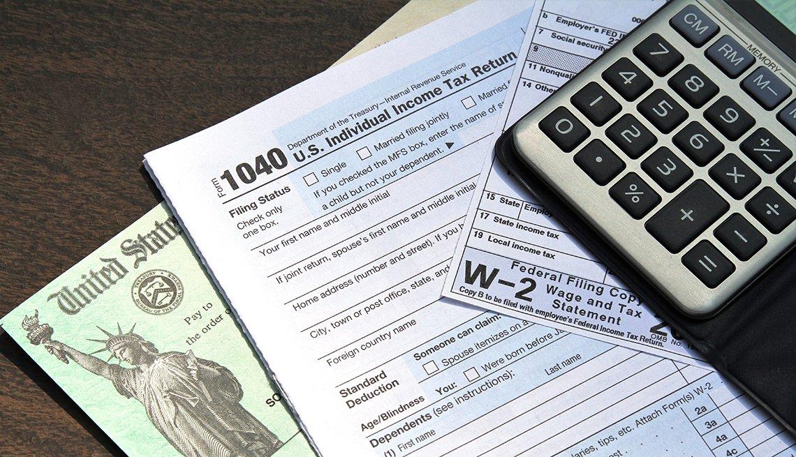 Cheque del Tesoro de Estados Unidos, formulario 1040 y W-2 del IRS, y una calculadora.
