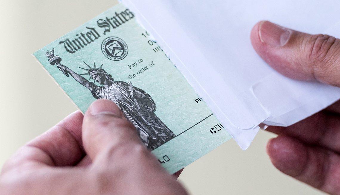 Manos sacando un cheque del tesoro de Estados Unidos de un sobre.