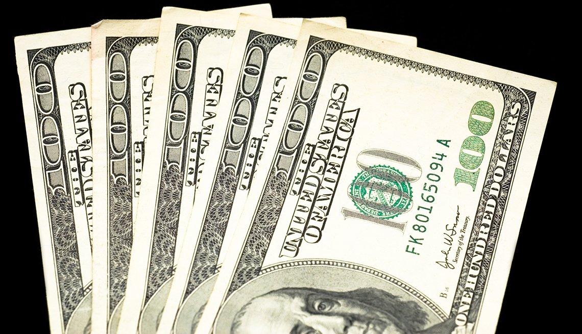 5 billetes de 100 dólares sobre un fondo negro.