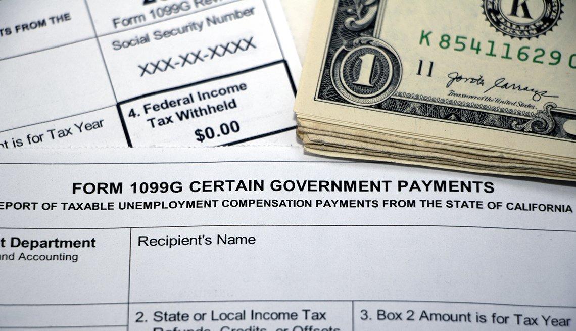 Formularios 1099G, y de impuestos federales debajo de un fajo de billetes de dólar.