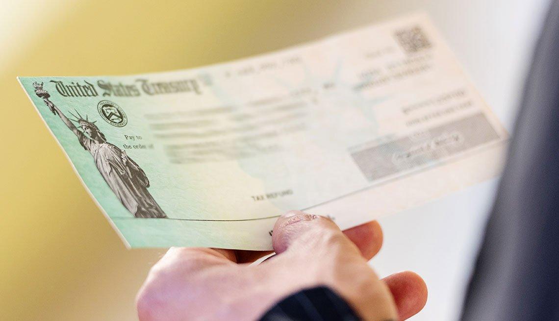 Mano de una persona sostiene un cheque del Departamento del Tesoro de Estados Unidos