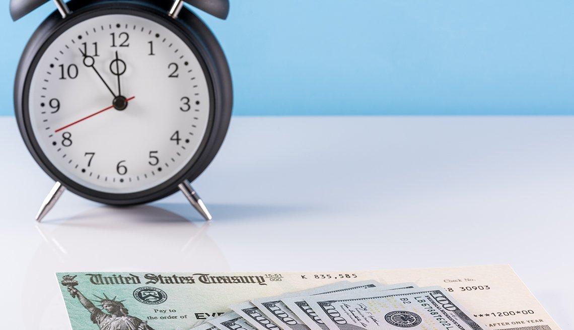 Reloj despertador de cuerda con billetes de 100 dólares y bonos del tesoro.