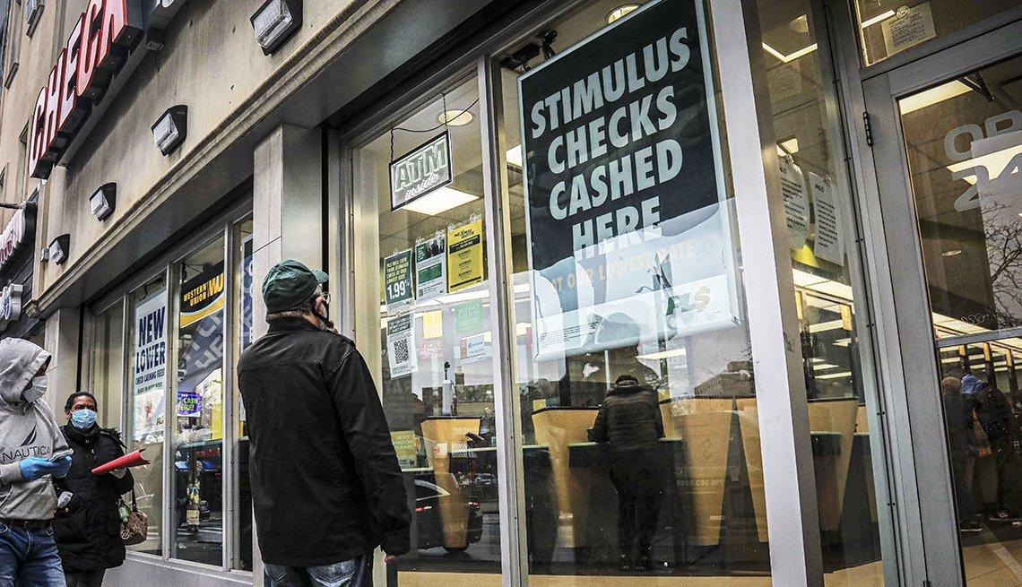 Personas con máscaras afuera de un centro de cambio de cheques de estímulo por efectivo en Brooklyn, Nueva York.