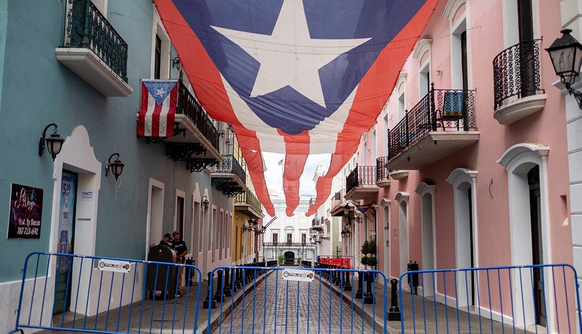 Vallas bloquean el acceso a una calle que en medio tiene la bandera de Puerto Rico sostenida de las casas en el Viejo San Juan, Puerto Rico.