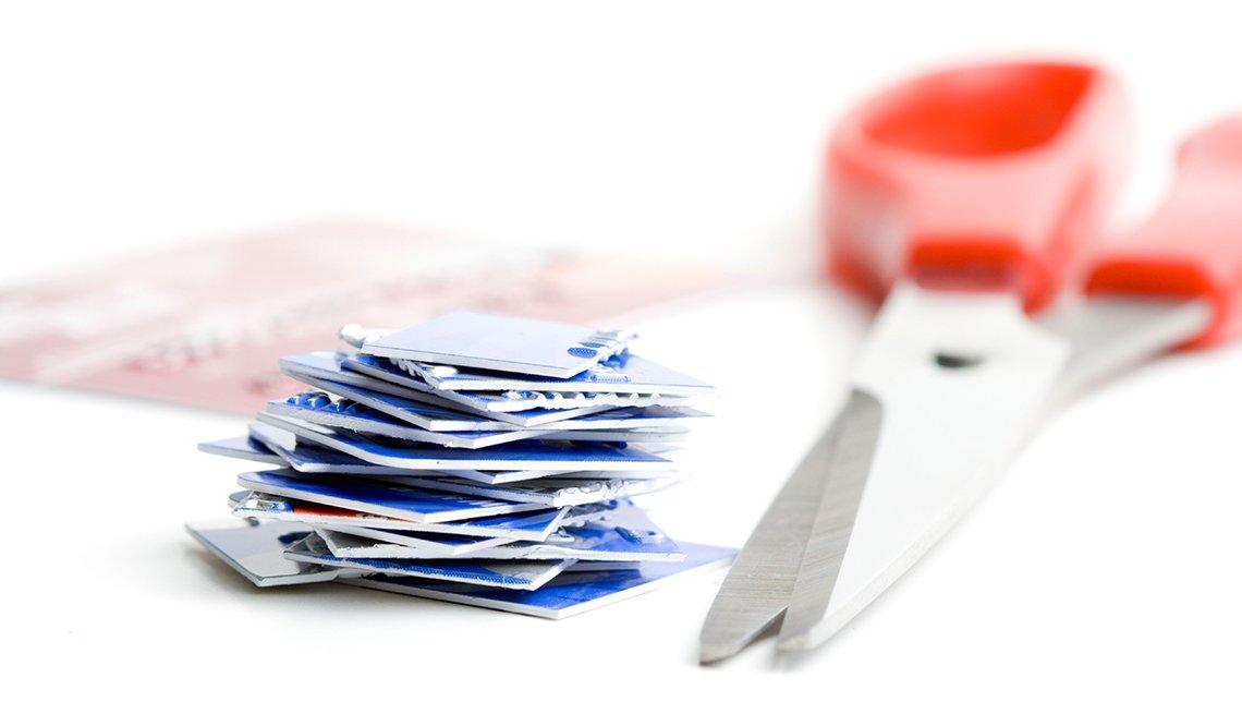 Una pila de tarjetas de crédito cortadas y una tijera