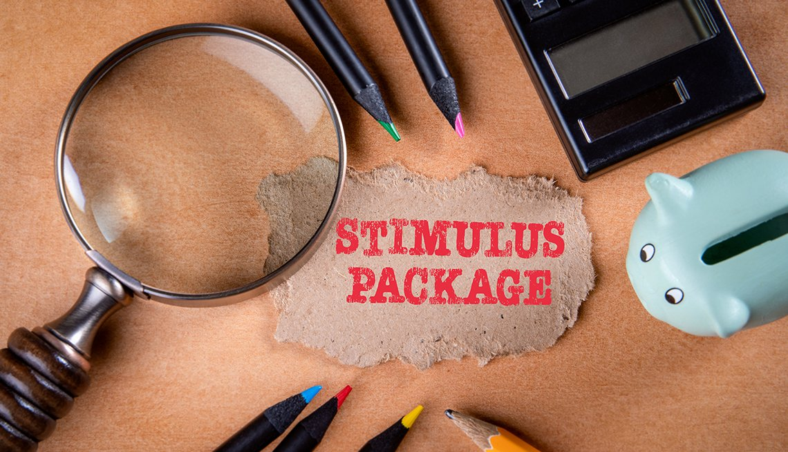 stimulus package note surrounded by magnifying glass, piggy bank, pencils and calculator on a table
