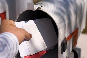 Mano de una persona recogiendo el correo de un buzón.