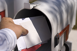 Male human hand pulling white envelopes from outdoor mailbox