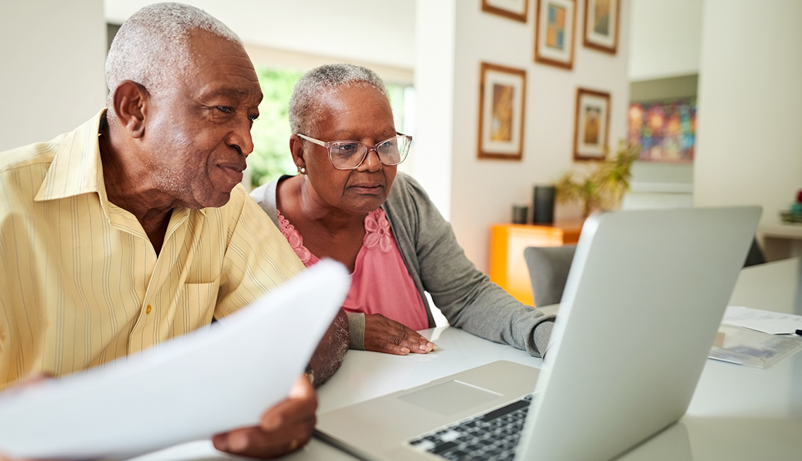 couple in home setting work together on financial paperwork and look at laptop computer screen