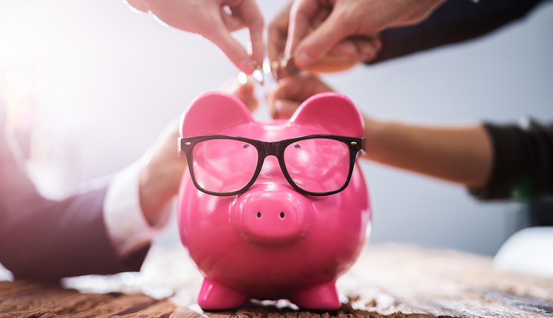 Alcancía rosada en forma de chochinito con lentes y varias personas colocando monedas.