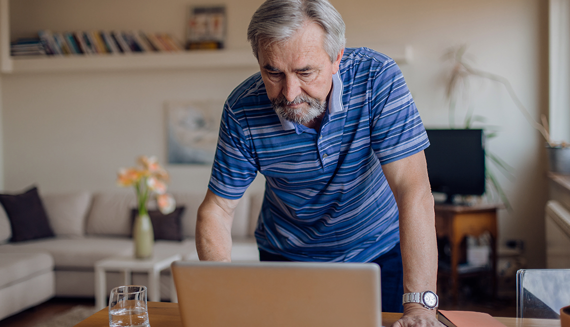 man standing over open laptop looks at computer screen