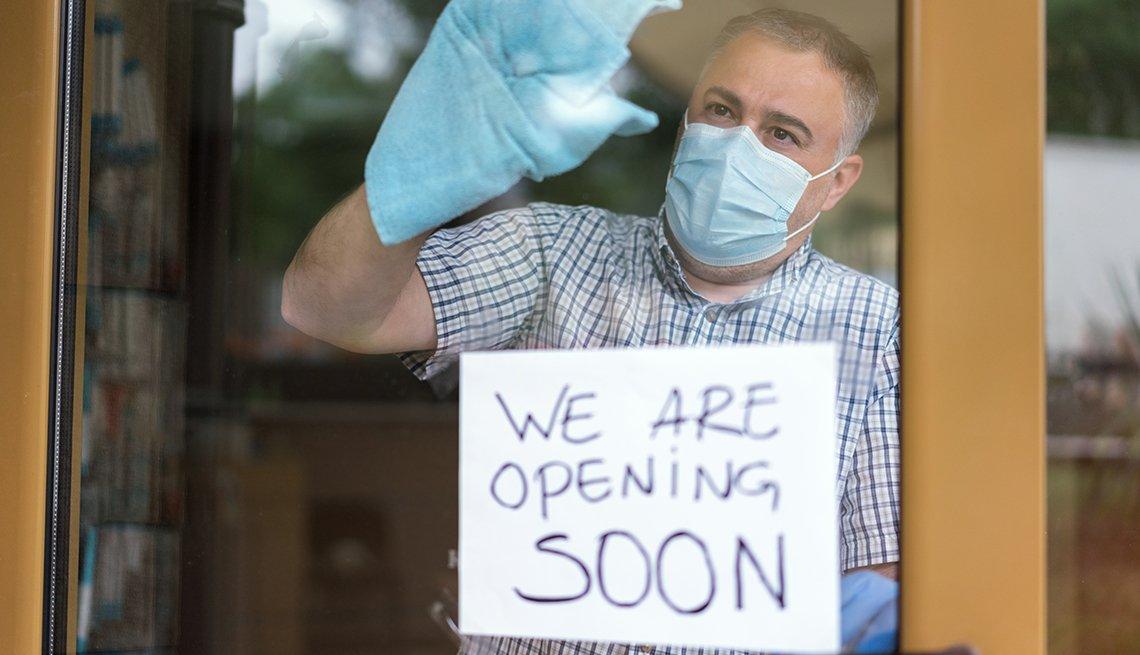 Hombre con tapaboca y guantes limpiando la puerta de entrada a un negocio con un letreo en inglés que dice abriremos pronto.
