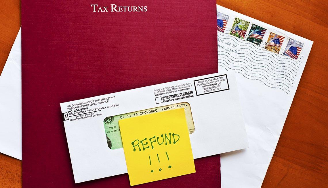 Carpeta roja con el letrero en inglés que dice reembolso tributario, un sobre cerrado del IRS y una nota que dice reembolso.