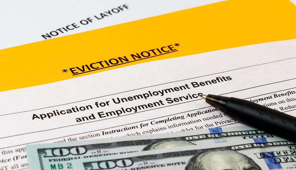 Billetes de 100 dólares encima de una aplicación de beneficios de desempleo, y una notificación de desalojo.
