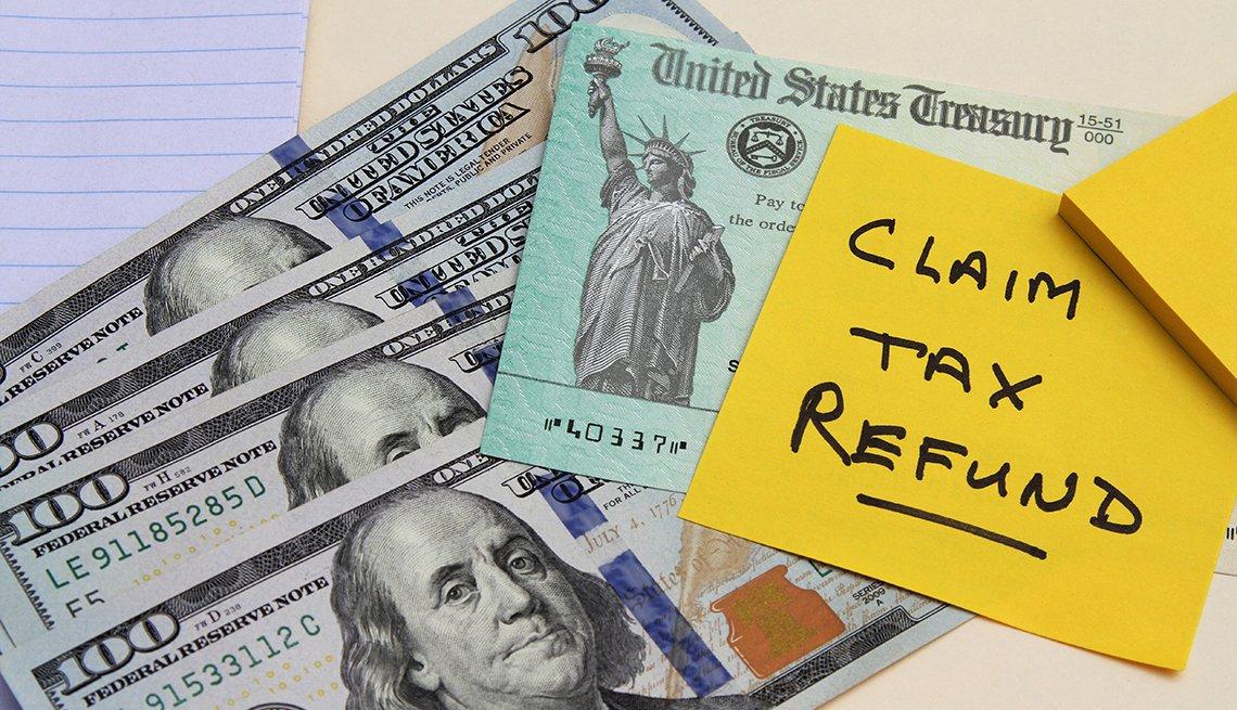 Billetes de 100 dólares, cheque del tesoso y una nota en inglés que dice reclamar reembolso de impuestos.