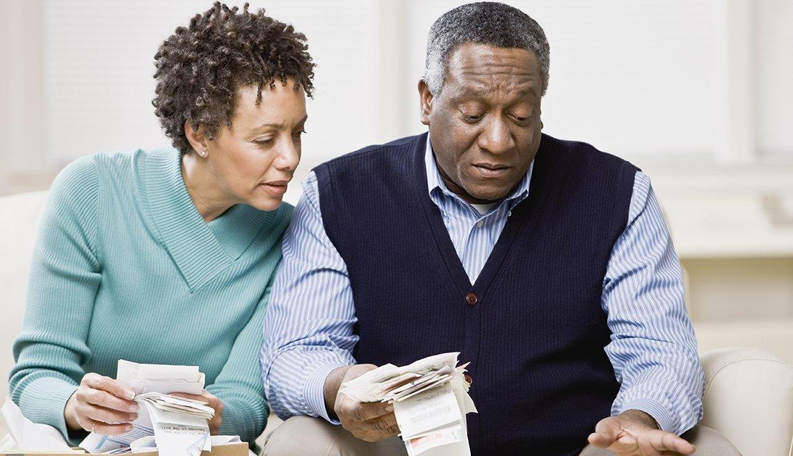 Pareja mayor revisando facturas de compras en la sala de su hogar.