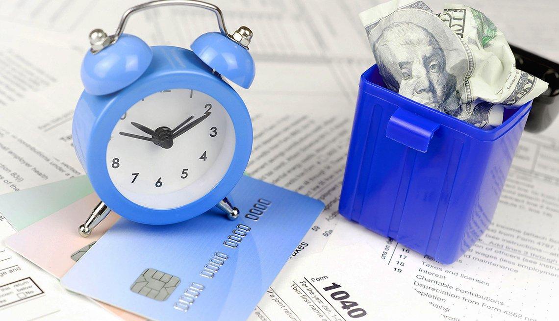 Formularios 1040 del IRS debajo de un reloj despertador y al lado de cubo con dólares.