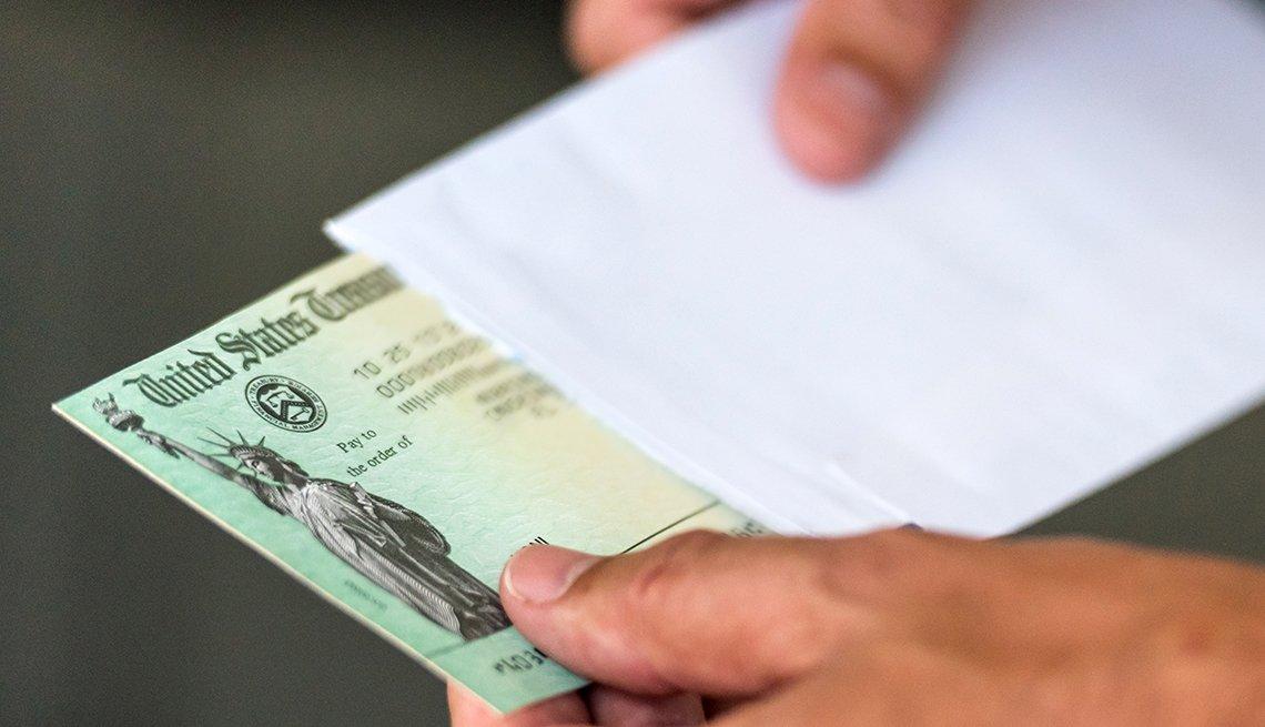 Manos de una persona sacando un cheque del Departamento del Tesoro de los Estados Unidos de un sobre.