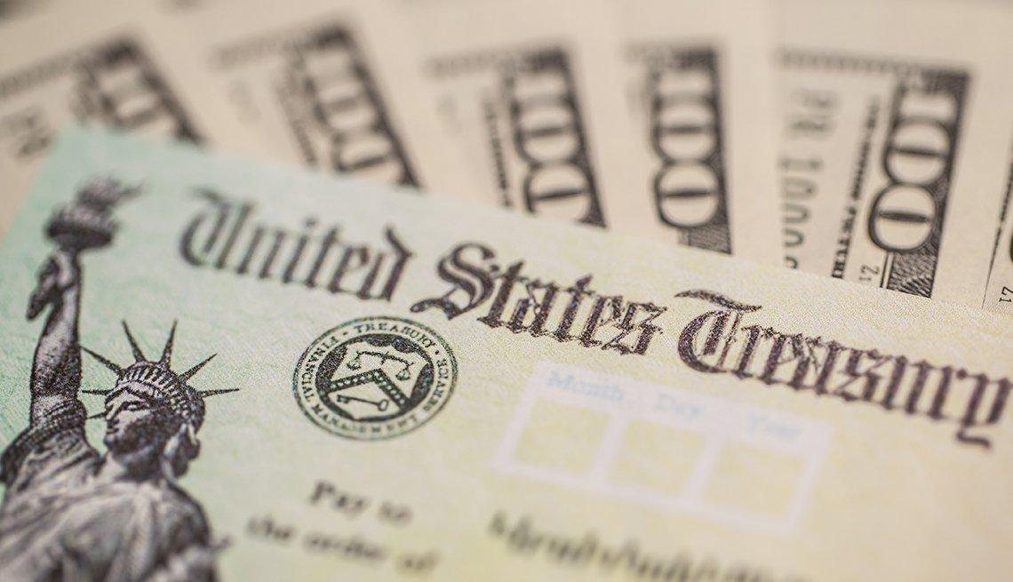 Cheques de estímulo alrededor de billetes de $100 dólares.