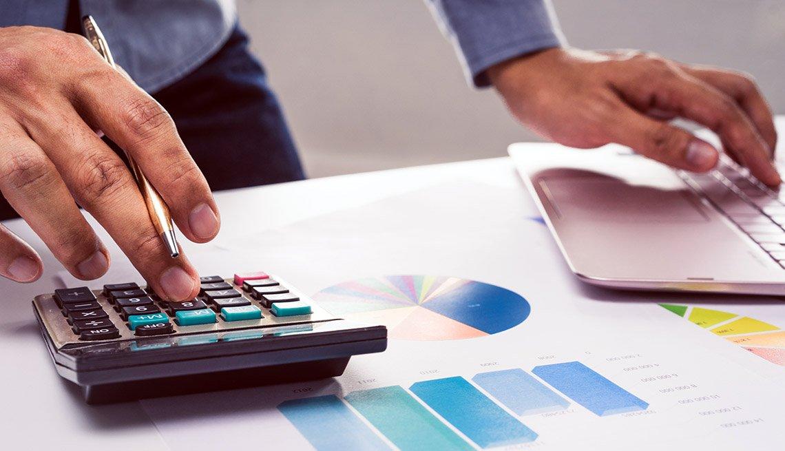 Manos de una persona sobre una calculadora y hojas con gráficas estadísticas.
