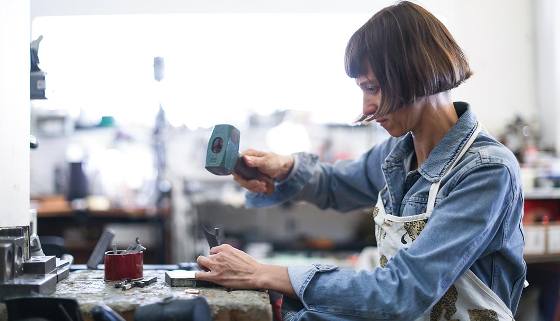 Fabricante de joyas en su taller con un martillo en la mano.