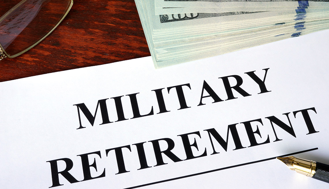 "a bundle of hundred dollar bills and a piece of paper says ""military retirement"" on a desk"