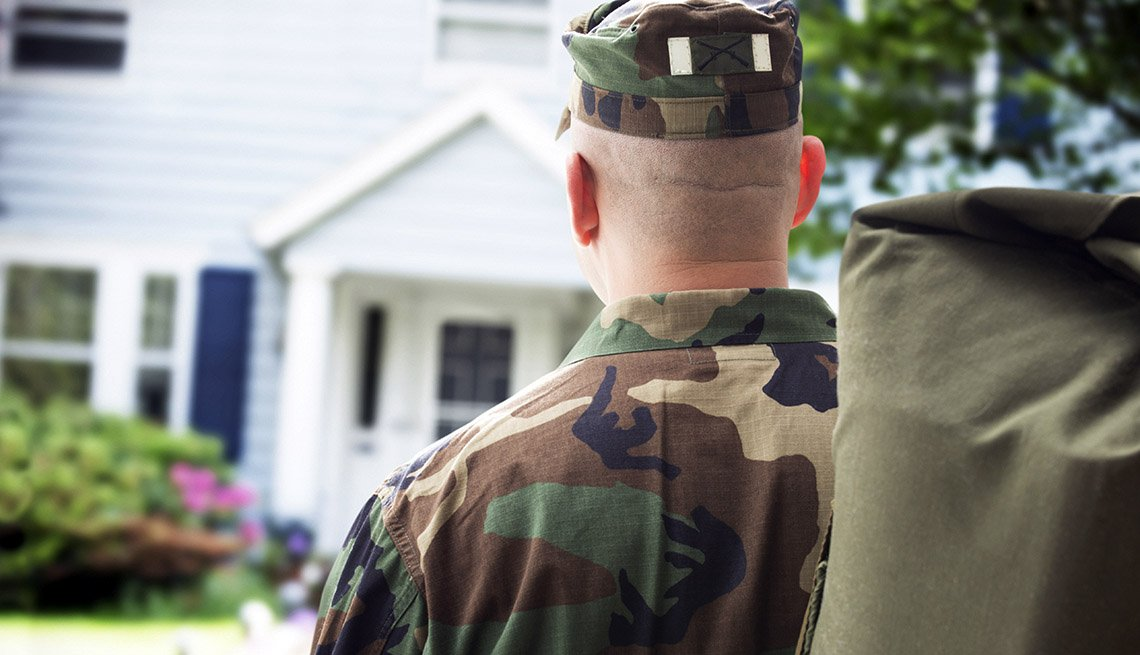 the back of a service member carrying duffel as he returns home and walks to front door