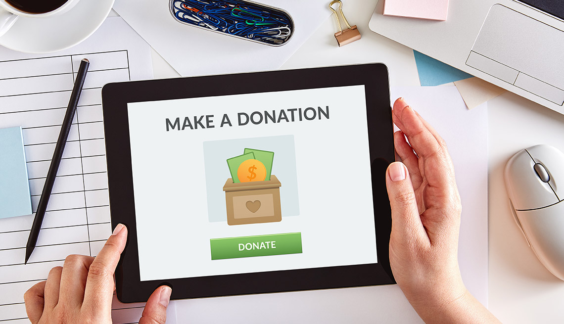 Hands using a digital tablet to donate money to charity