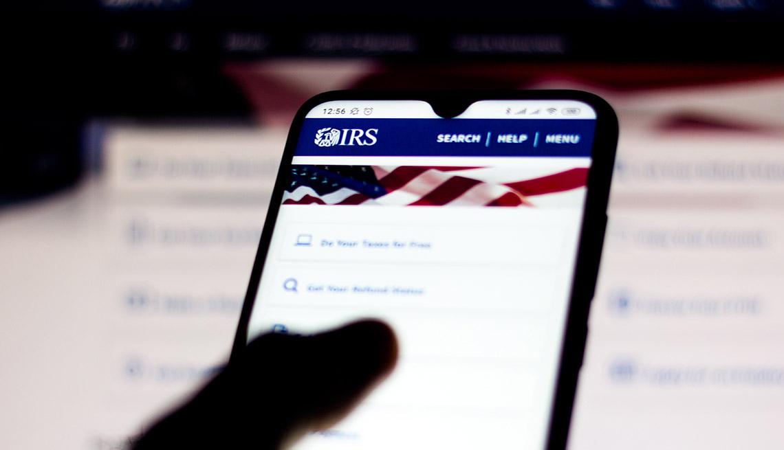 Persona sosteniendo un teléfono móvil con la página del IRS en la pantalla.
