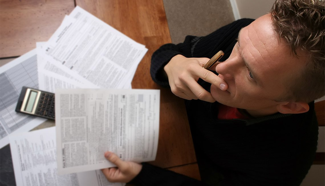 A birds eye view of a man reading the IRS instructions as he is doing his taxes