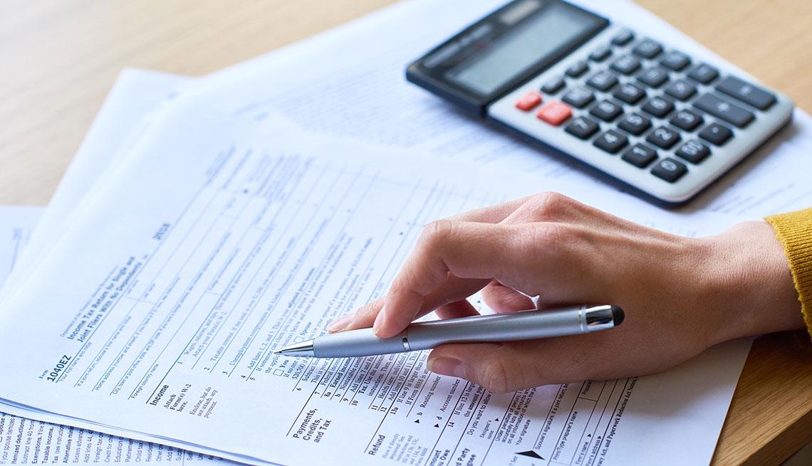 Manos de una persona sobre formularios del IRS al lado de una calculadora.