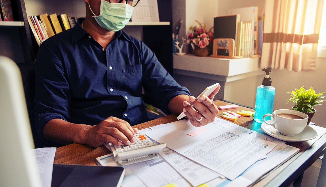 tax preparer wearing mask during pandemic calculates income tax at a desk with forms spread across surface
