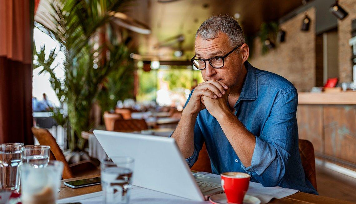 Un hombre sentado frente a su computadora se muestra pensativo