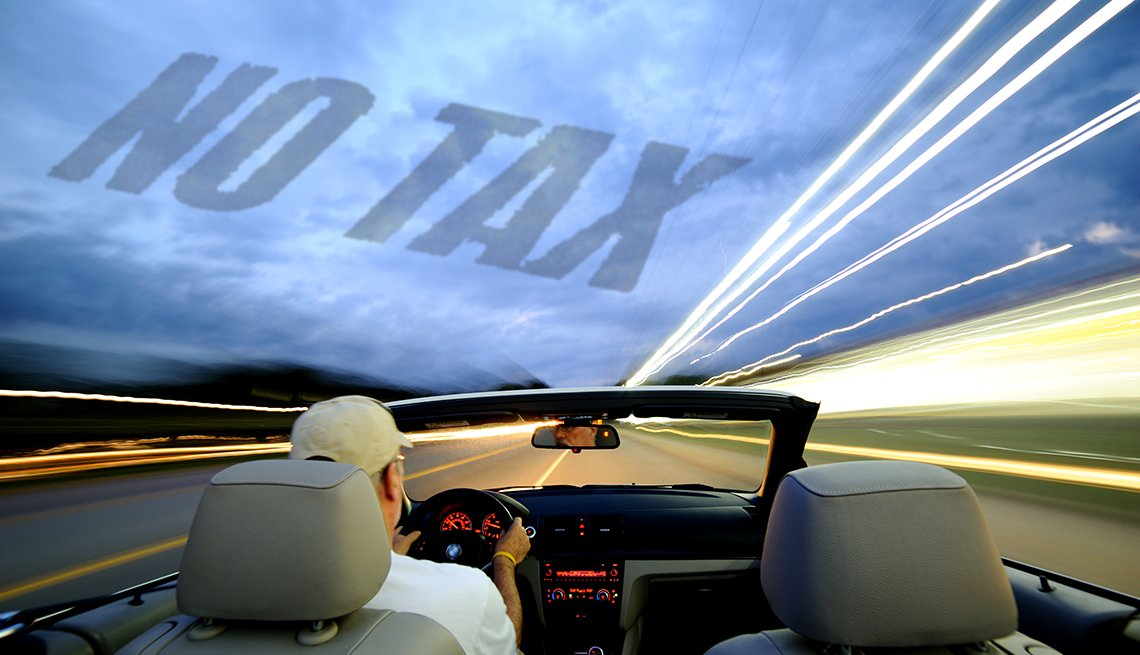 view of man driving open top convertible car towards an unknown destination - the words NO TAX  are superimposed in the sky