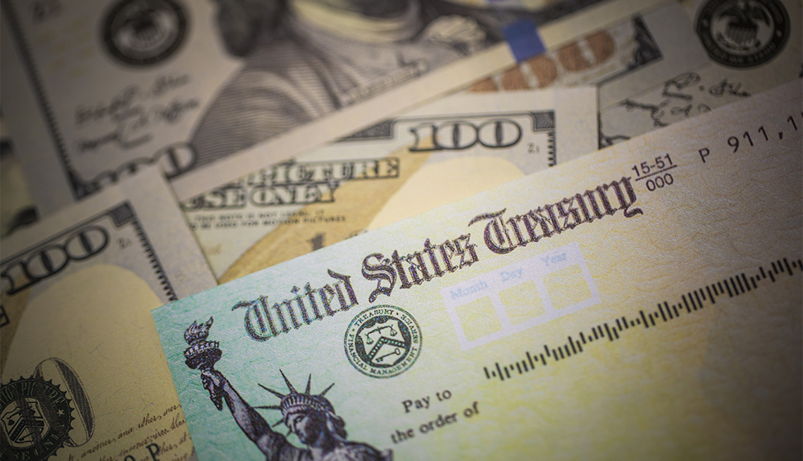 Cheque de estímulo del Departamento del Tesoro de los Estados Unidos encima de billetes de $100 dólares