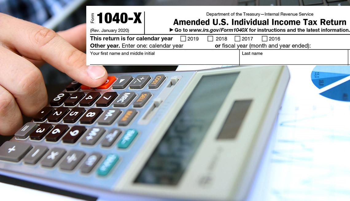 Mano de una persona haciendo cuentas en una calculadora y la parte superior del formulario 1040 del IRS