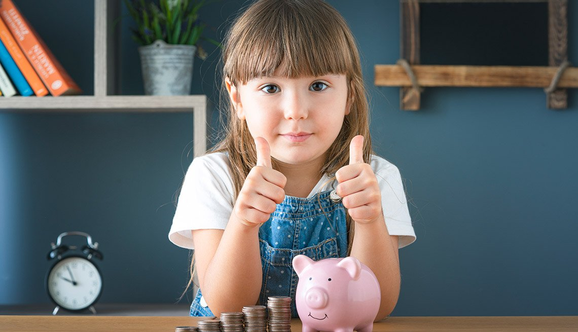 girl giving the thumbs up to saving money as she poses with her piggy bank and piles of coins