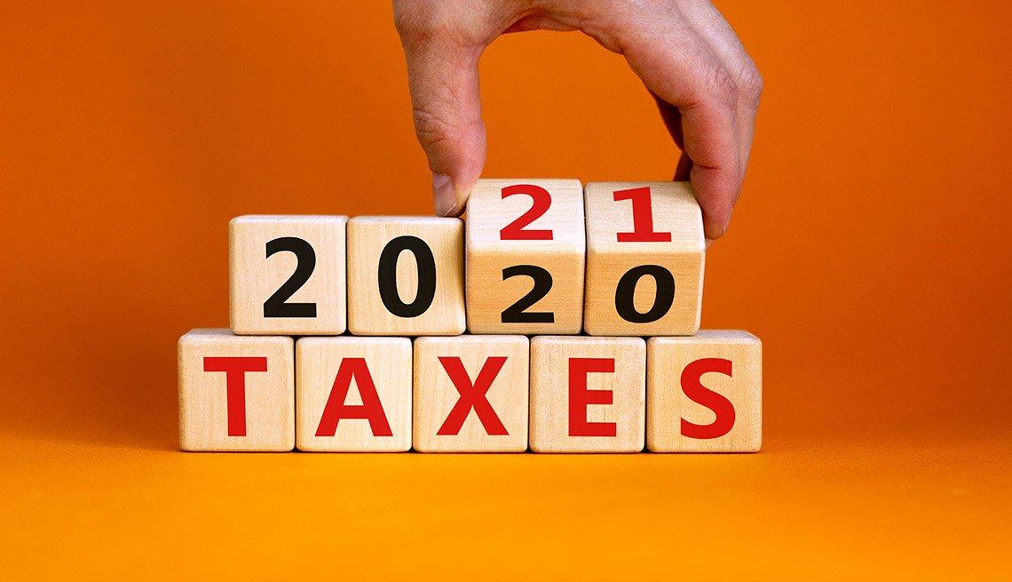 Mano cambiando al año 2021 en unos cubos de madera apoyados en otros que dicen impuestos.