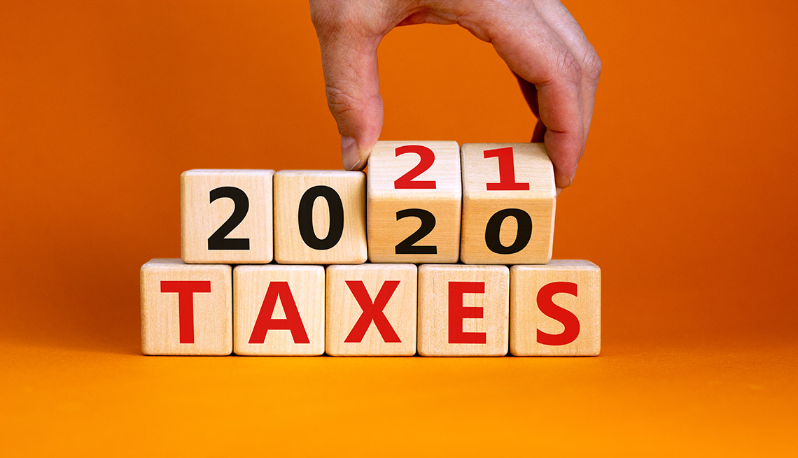 a hand reaching into the top of the photo is  flipping wooden cubes that spell out 'Taxes 2020' to 'Taxes 2021'