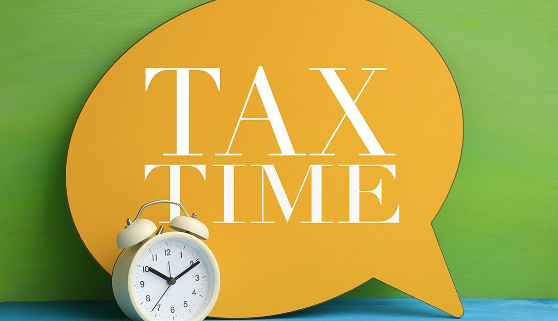 "a bright orange sign on a green background says ""Tax Time"" with an alarm clock in the foreground"