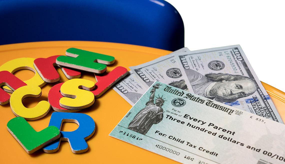 Letras en madera al lado de un cheque del Tesoro de los Estados Unidos y billetes de 100 dólares