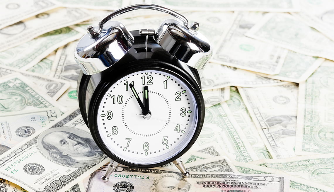 A dial alarm clock nearing midnight sits on a pile of U.S. paper currency money.
