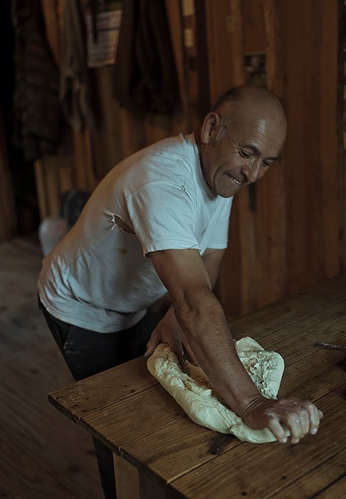 CHILE. 2019. Arturo bakes bread twice a week with the flour they bring from Bariloche, the closest town to the valley, where Horaldo goes every three months to buy provisions. They have to cross the border to Argentina in a 5 hour journey by horse, boat and bus.