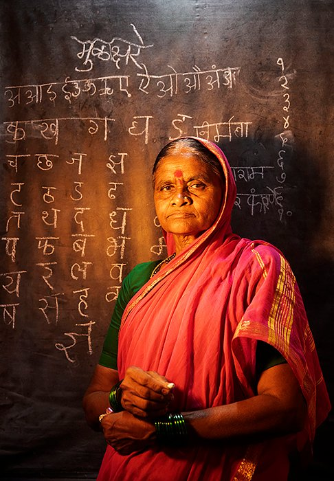 INDIA. Phangane Village, Maharastra. 2019. This grandmother, like many in the village, practices the Marathi alphabet along with her grandchildren diligently every evening.