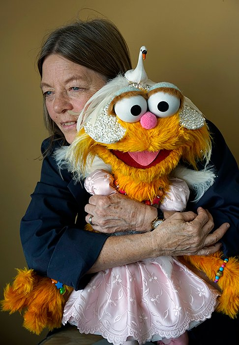 USA. Queens, New York. 2019. Rollie Krewson photographed at the Jim Henson Company's Long Island City, Queens, workshop, next to Zoe, a Sesame Street puppet that she designed. Rollie Krewson photographed at the Jim Henson Company's  workshop. Krewson is a puppet designer and builder known for her work on various Muppet productions. She interned with Jim Henson's company in the mid-1970s. Although she now works primarily as a designer/builder, she began as a performer, doing small bits on The Muppet Show and other projects. She has contributed to almost every Henson production since her arrival, and to this day carries her skills through on Sesame Street. Krewson has received seven Daytime Emmy Awards for her contributions on Sesame Street and has been nominated many times for her work on other Henson productions.