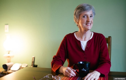 Caregiver Margaret Sweasy sits for a portrait in her home, WA State News