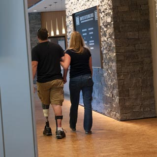 A wounded warrior and friend walk into the kitchen area. Veterans Day 2013. (Cherie Cullen/USO)
