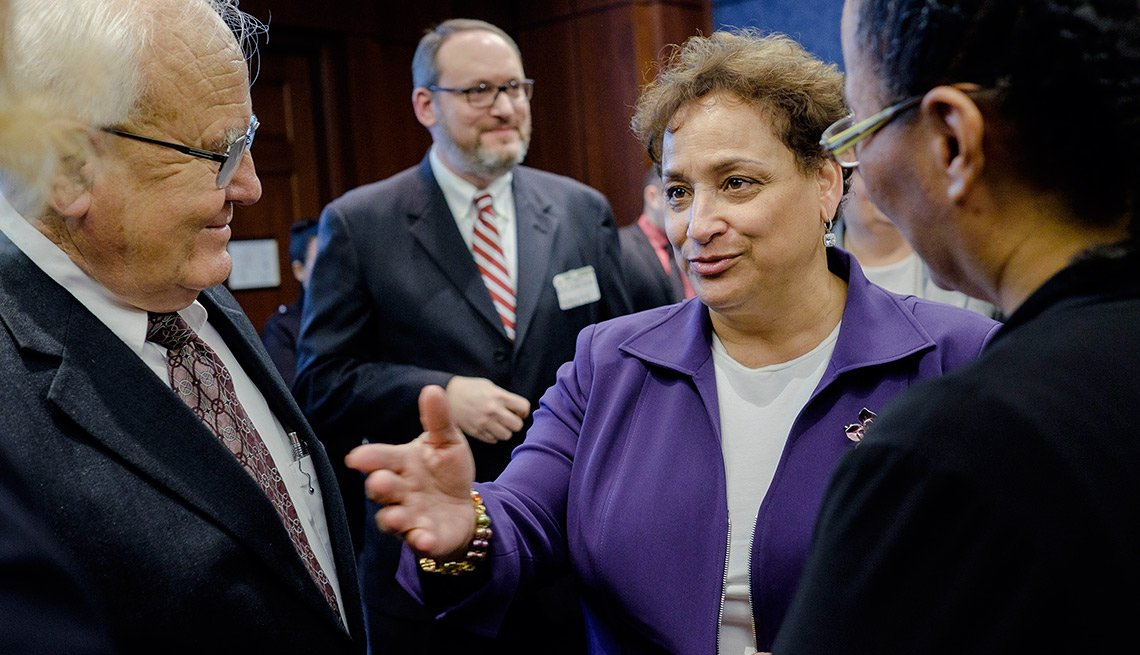 AARP CEO Jo Ann Jenkins, center, talks with caregivers Marianita Gorman, right, and Don Schierling, left, as lawmakers and AARP officials announce the launch of the bipartisan, bicameral Assisting Caregivers Today caucus in Congress at the U.S. Capitol on March 3, 2015 in Washington, DC.