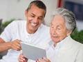 Hombre joven ayudando a una mujer mayor con la tecnología