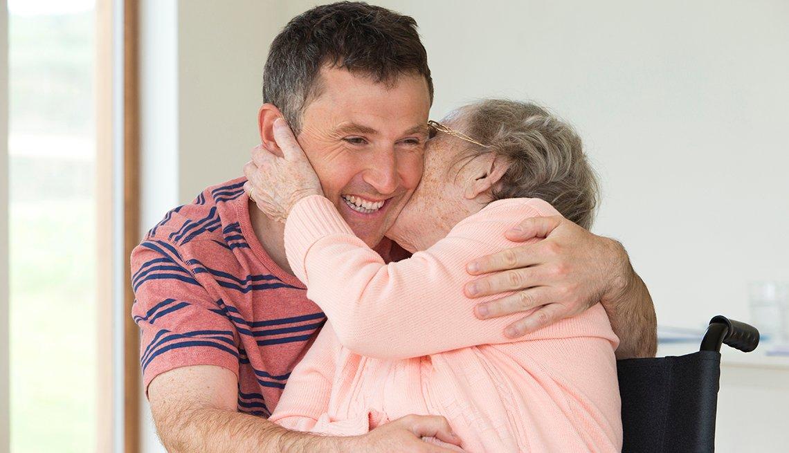 Una mujer en una silla de ruedas le da un beso en la mejilla a un hombre joven mientras la abraza